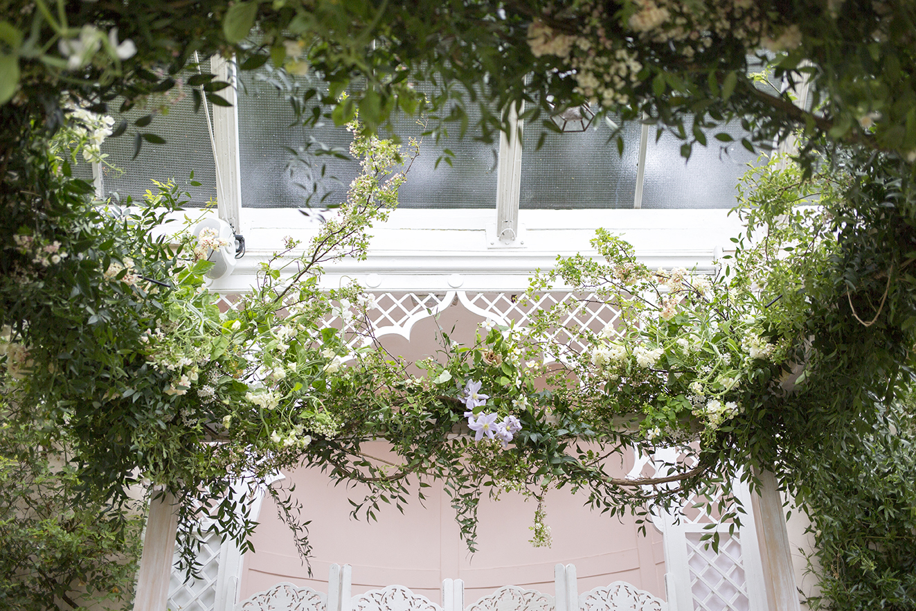 Installation | The chuppah, dressed with clematis vines, hawthorn, spring blossom, sweet pea and potato vines, and garden roses, for David and Tash's wedding ceremony, in the ornate curved Orangery at  Sezincote House