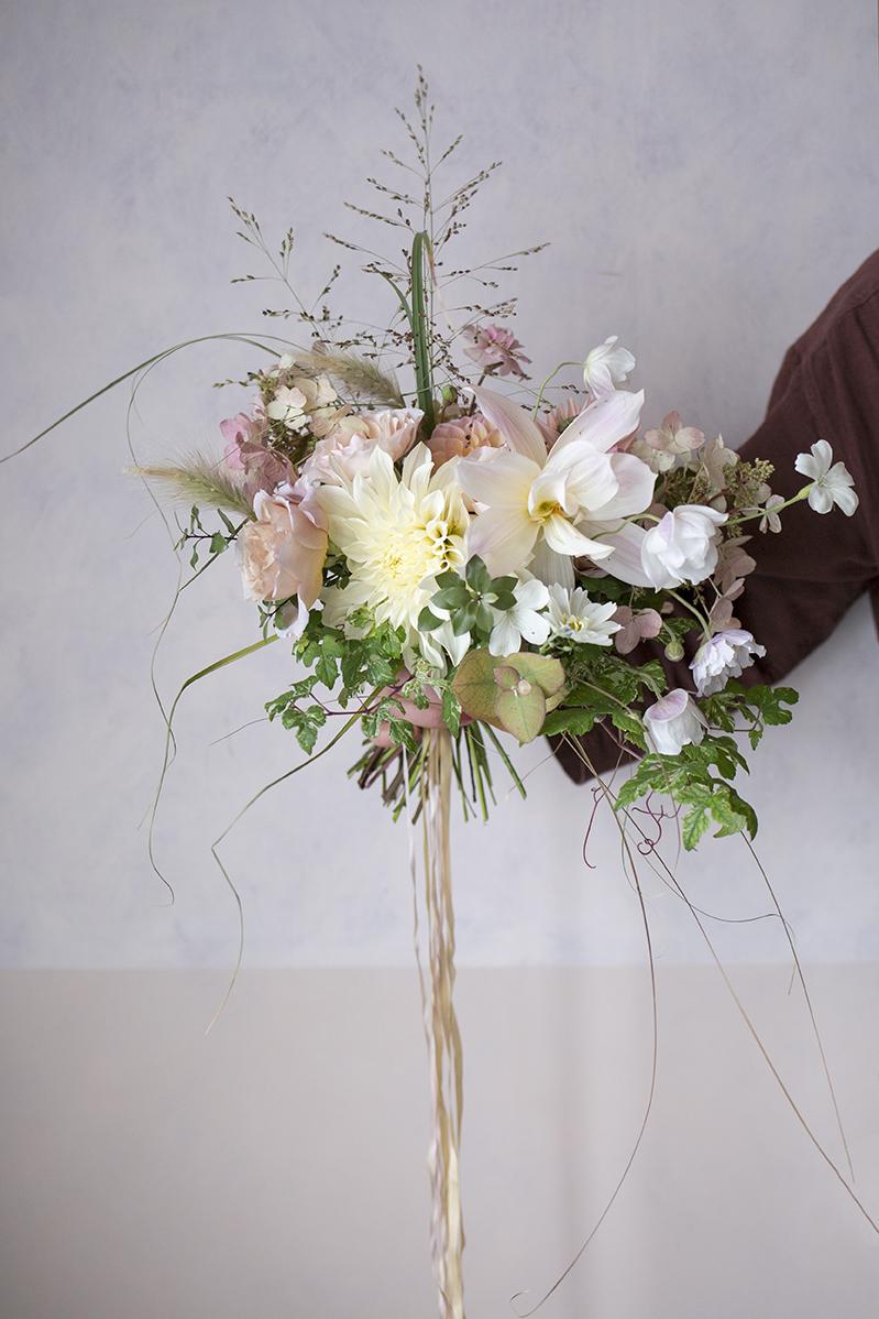 An autumnal bridal bouquet with cafe au lait dahlias, grasses and pale hydrangea blossoms