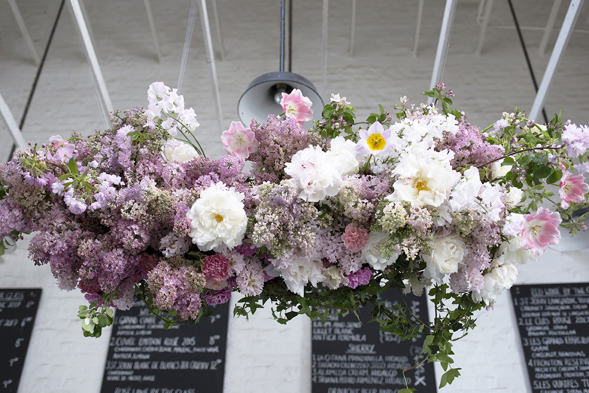A suspended 'flower cloud' installation of lilac, cherry blossom, tulips and ice-cream coloured peonies over the bar at  St John, Smithfield