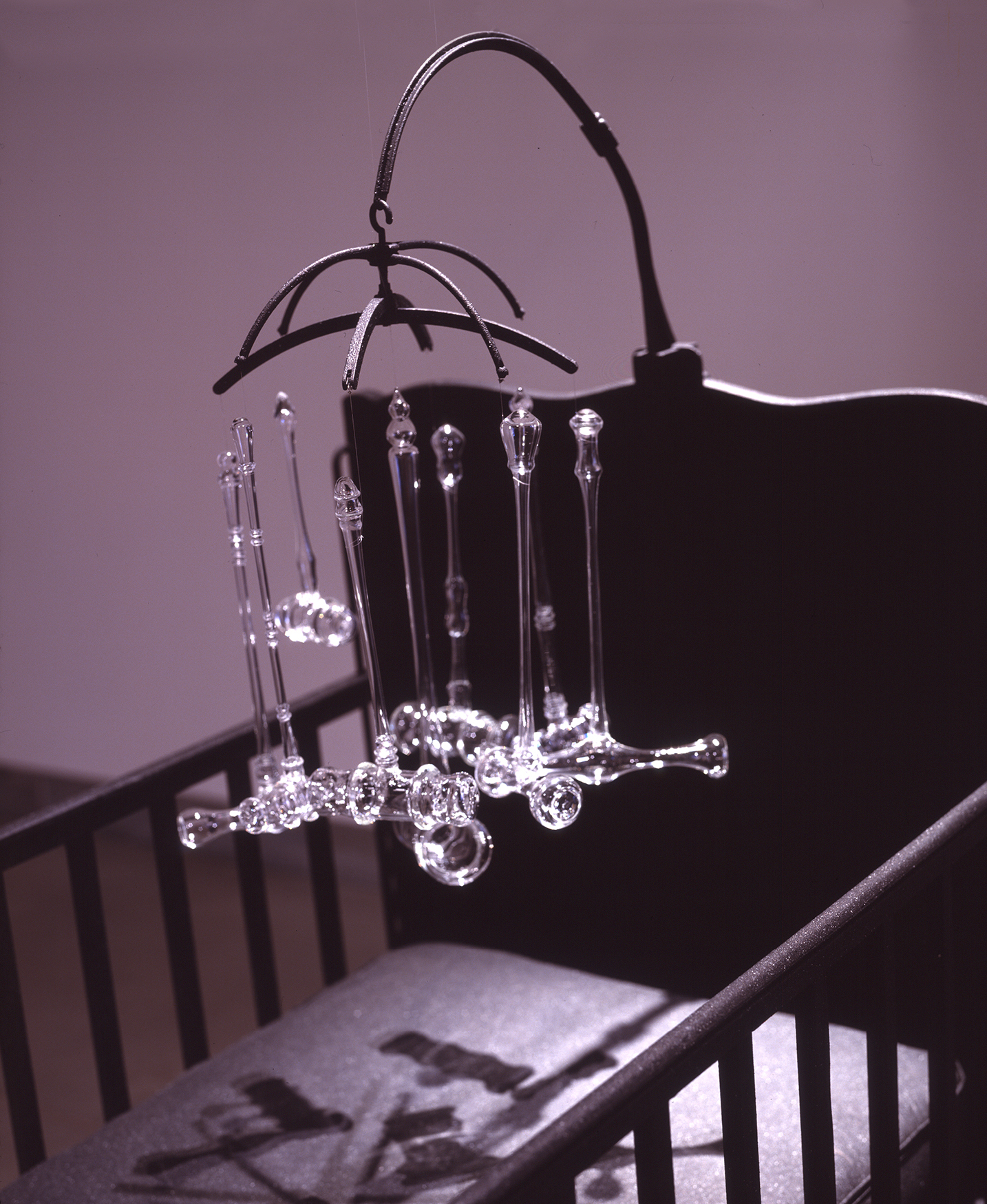 Detail of INFANT JUSTICE, 2002 crib with mobile consisting of nine glass gavels