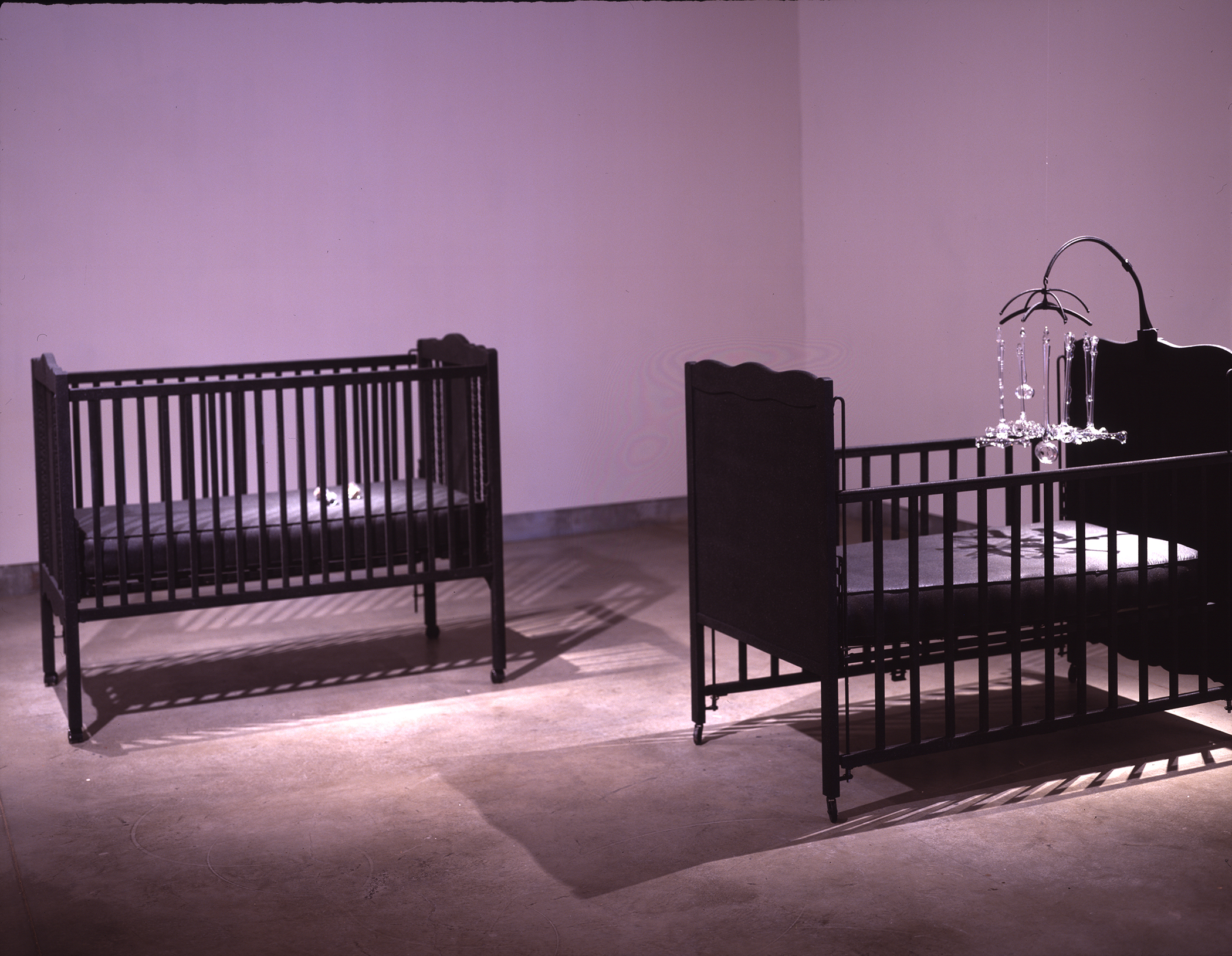 INFANT JUSTICE, 2002 crib with mobile consisting of nine glass gavels