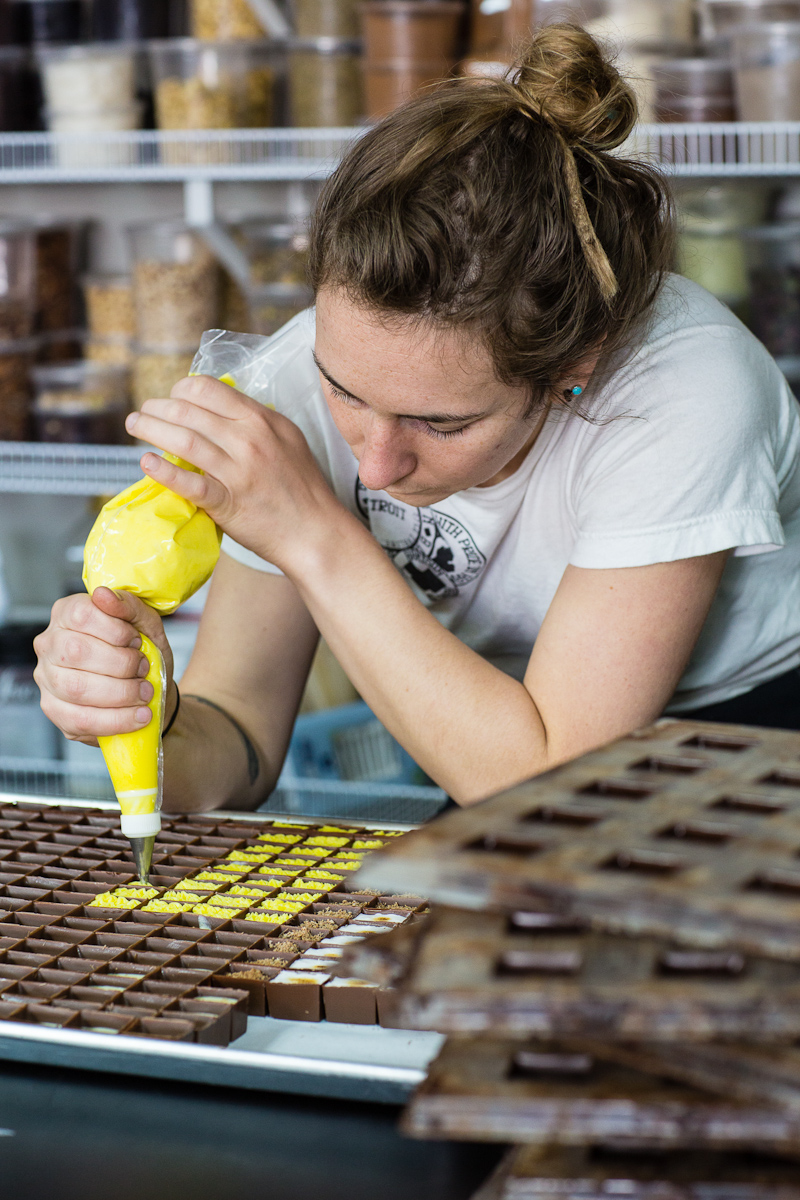 Bon Bon Bon Production Manager Carrie Hause pipes yellow buttercream frosting into milk chocolate shells creating Birthday Cake bonbons for retail Wednesday, June 3 at their shop in Hamtramck.