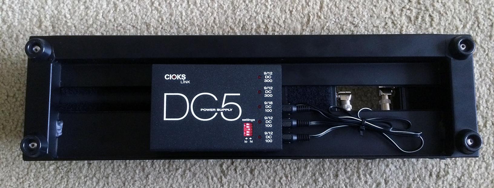 The Cioks DC5 power supply mounted under a Pedaltrain Nano+ pedalboard.