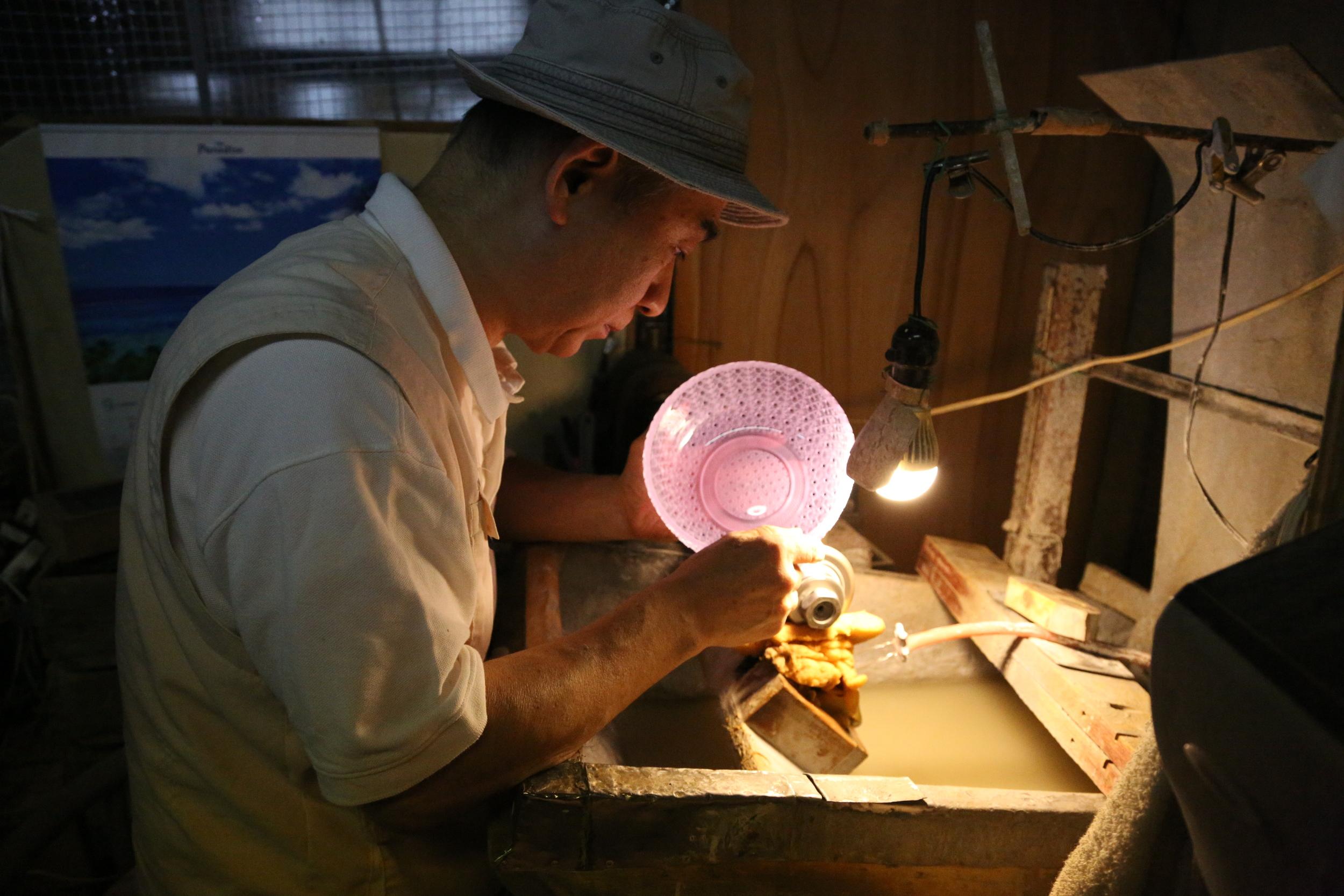Yoshiro Kobayashi cutting glass at his workstation. ©TOKI