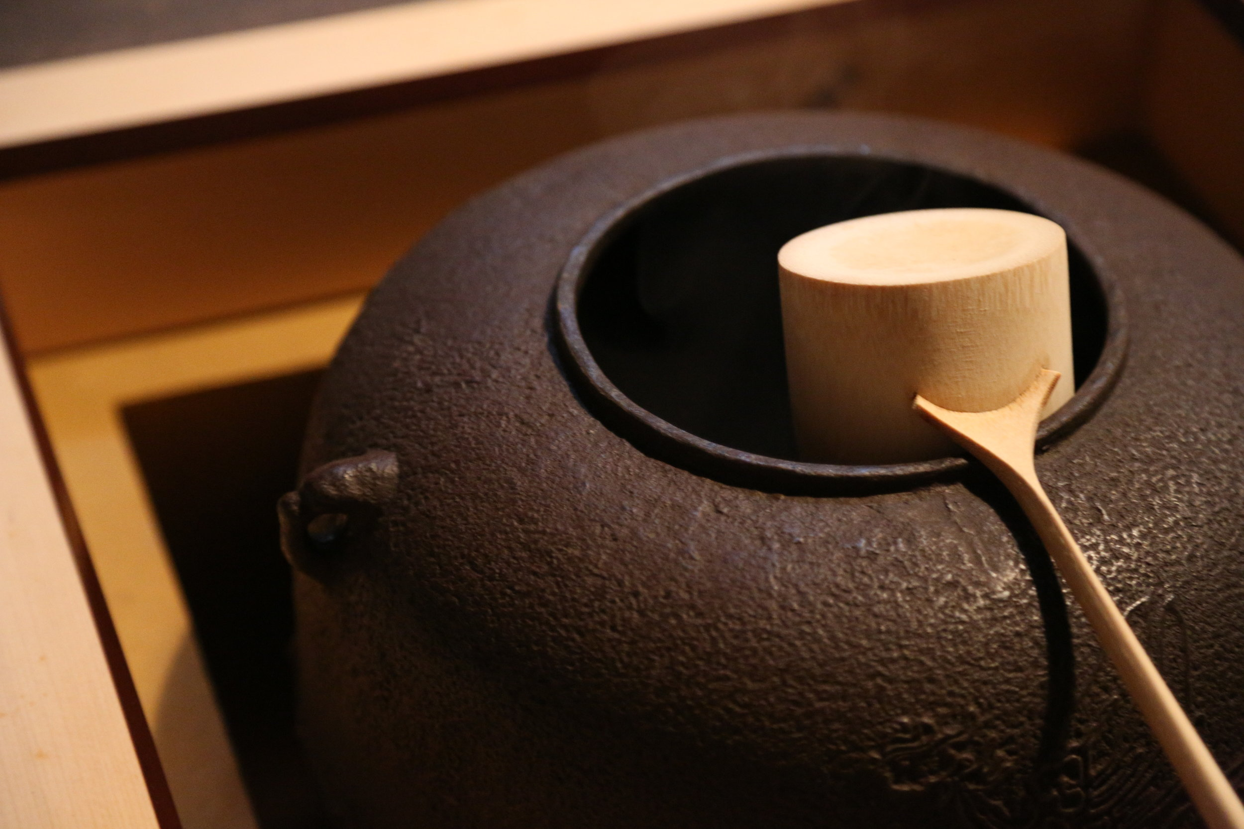 A larger iron pot (placed in the  ro  opening that contains an open flame) used to boil water for tea ceremony.  ©TOKI