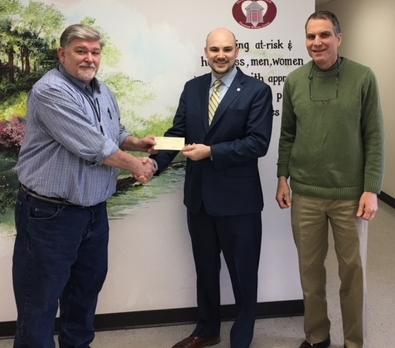 Matt Mitchel (center) presents a check to Brisben's Joe Hargrove (left) and Chris Payton.