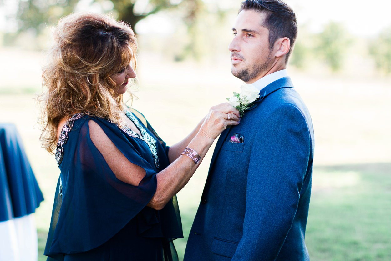 groom's mother pinning boutonniere