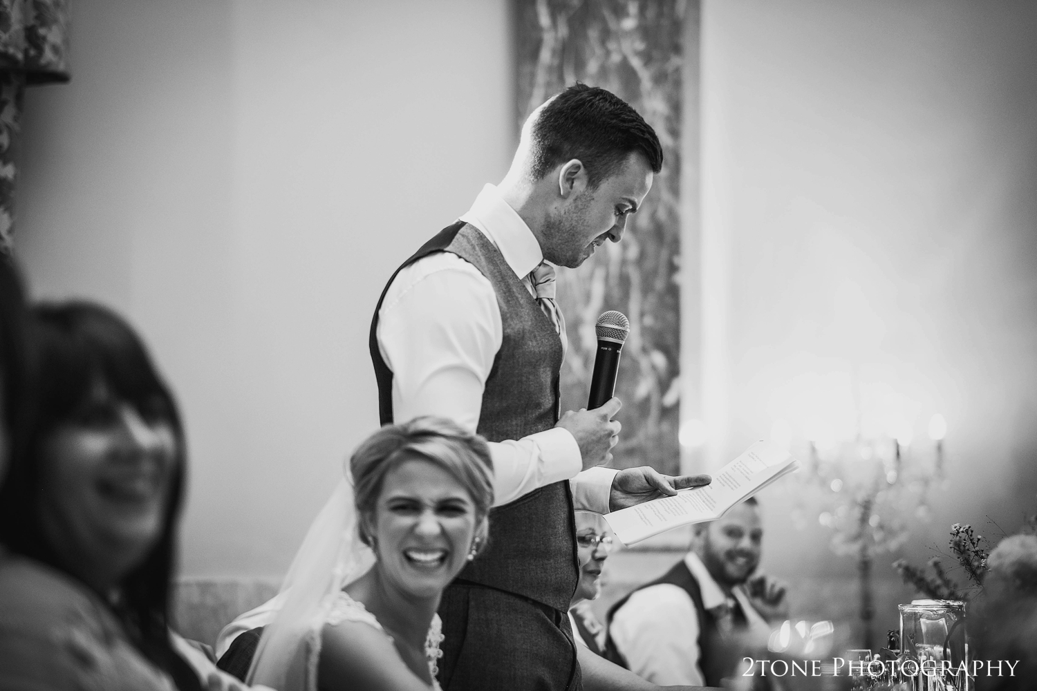 The groom stands and delivers a funny and witty speech that has his wife in fits of giggles.