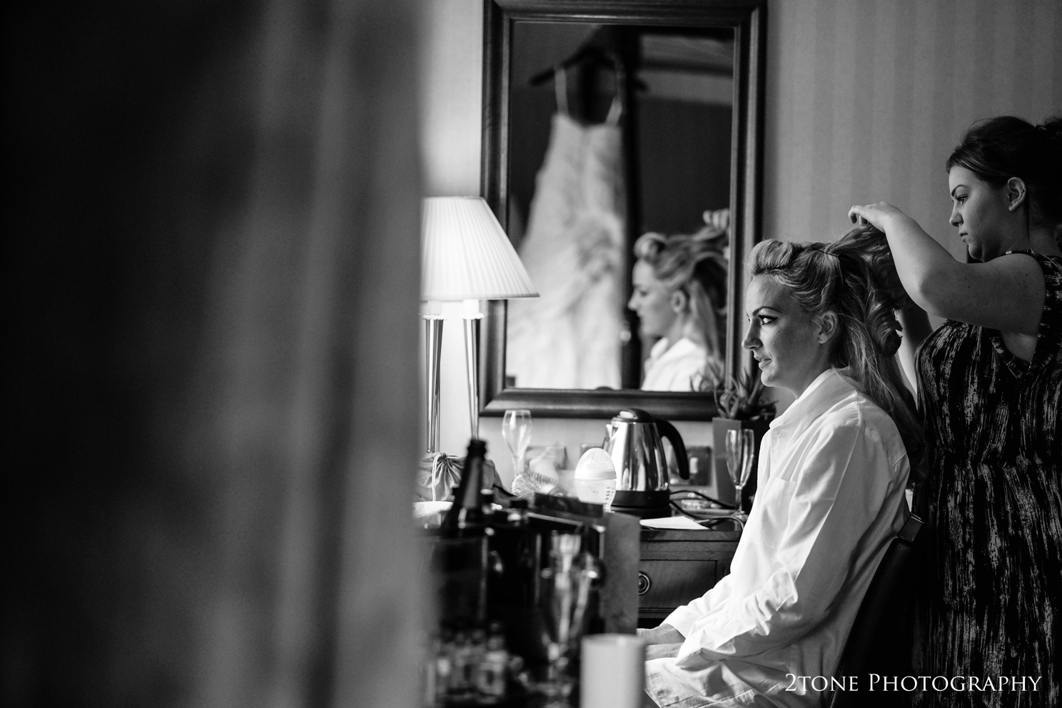 Sarah prepares for the wedding day ahead with her gorgeous Ian Stewart wedding gown hanging on the bed in the reflection of the mirror.