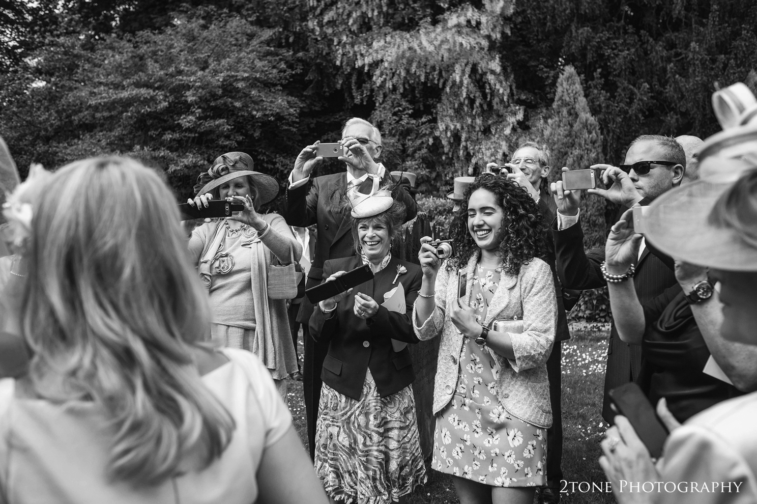 wedding guests with cameras at St Brandon's church, Brancepeth, Durham.  Wedding photography by www.2tonephotography.co.uk