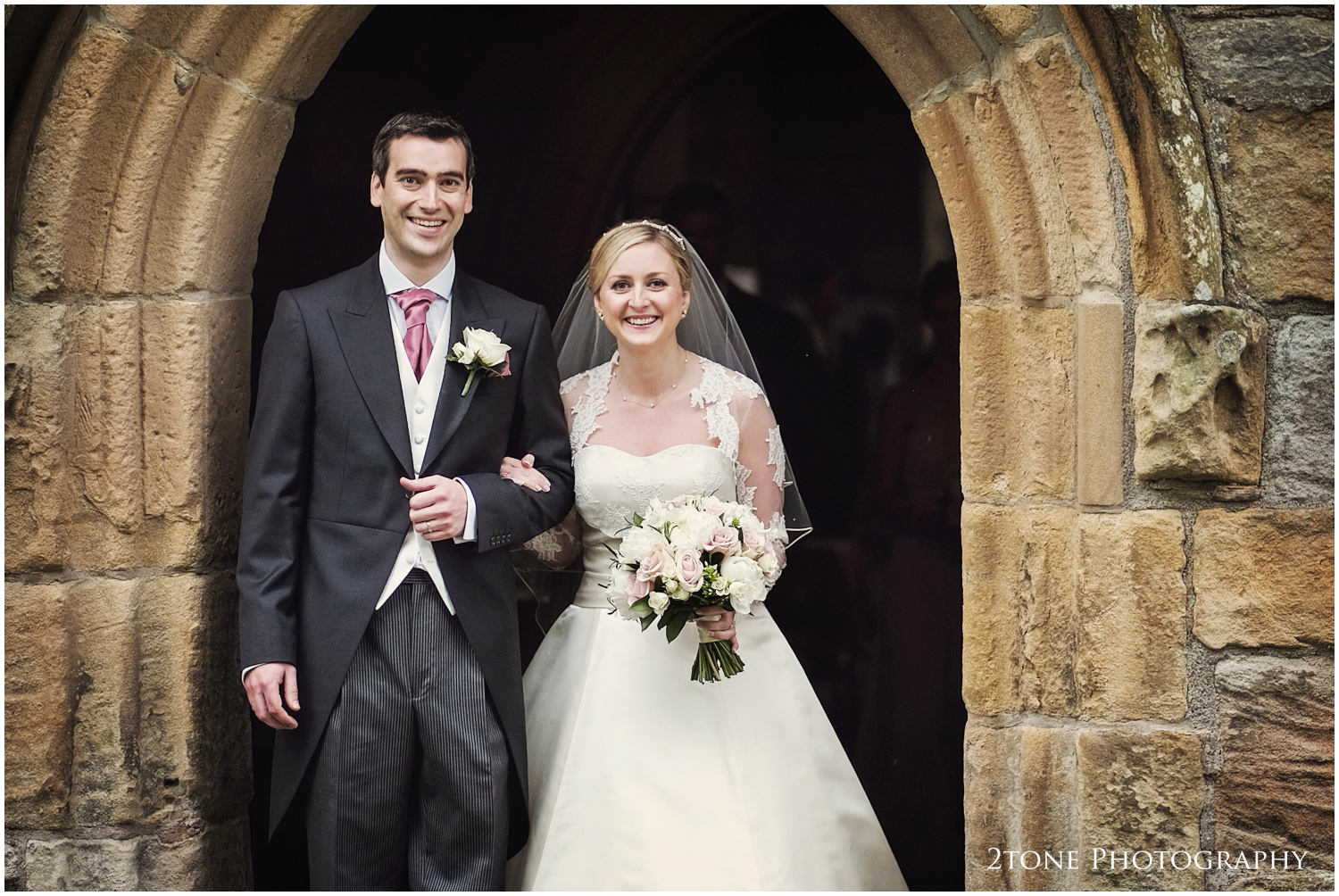 Our very happy newlyweds leave the church andenjoy a brief break in the rain with their guests.