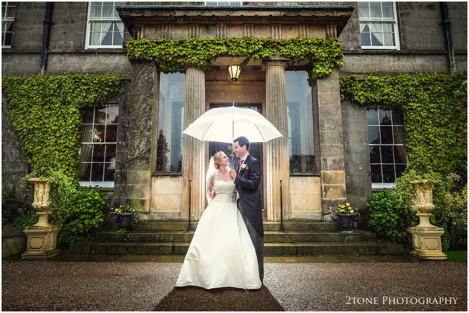 Rain on your wedding day doesn't have to be a bad thing. Rain can bring us a whole new set of possibilities such asreflections in puddles and this, look very carefully and you shall see how the rain droplets have been lit from behind so make them moreclearly visible. Romantic and charming.