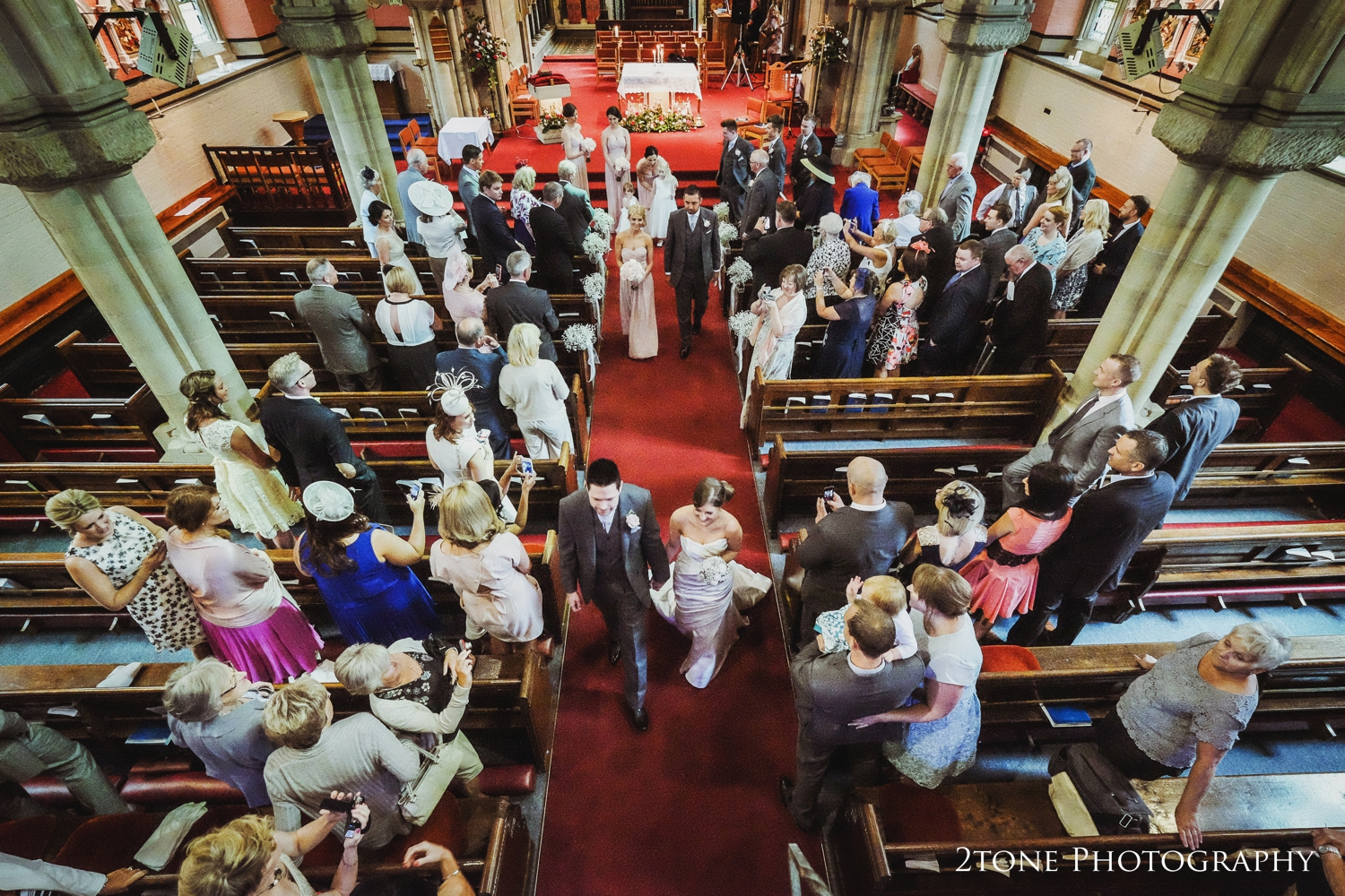 Standing looking from the gallery down into the church as Laura and Simon walk back down the aisle together gives us a different view of the scene that is normally seen. Guests standing watching, capturing the moment on their own cameras, the bridal party processing behind the newlyweds really capturing the mood of the moment.