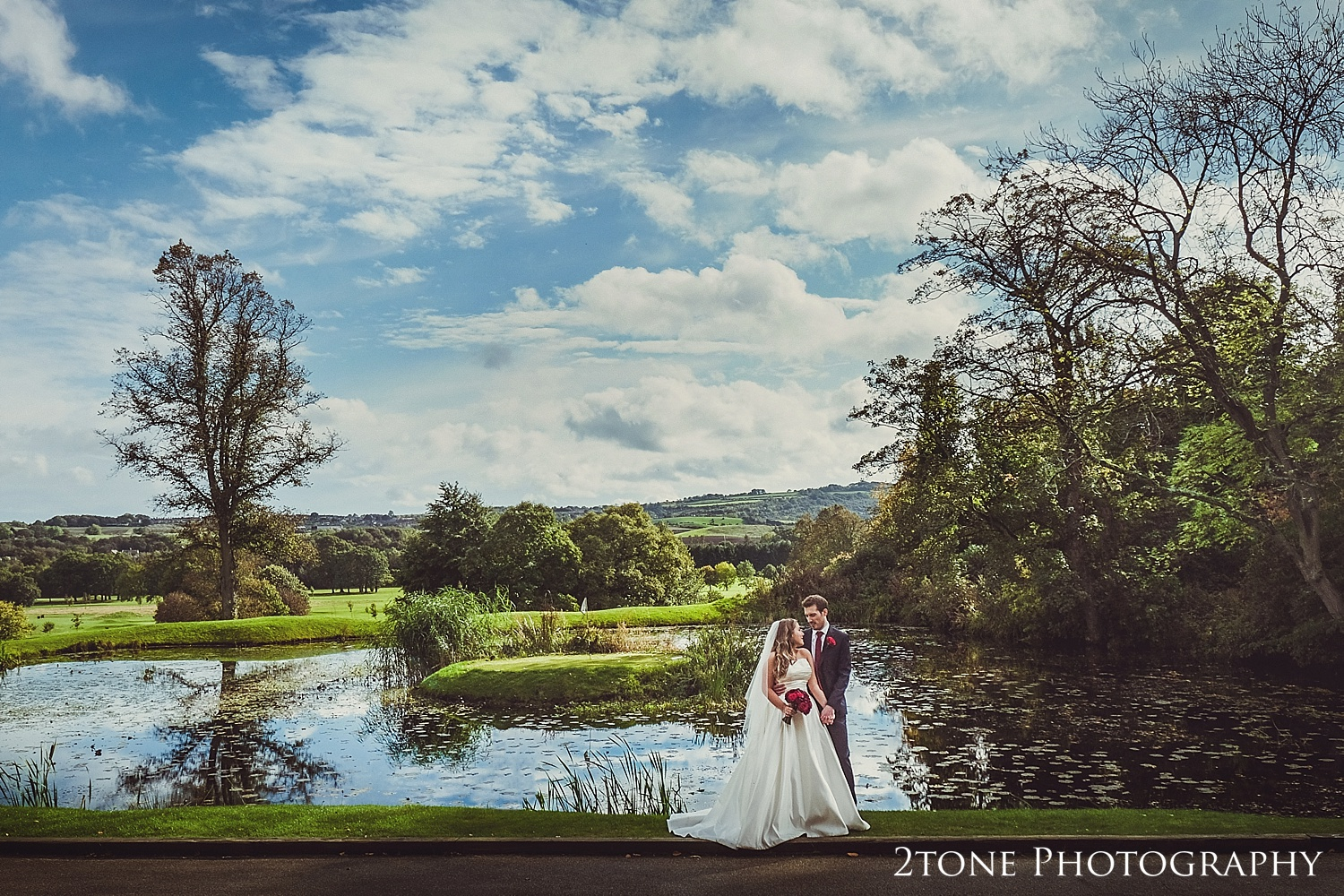 Bride and Groom standing next to a lake.  Wedding photography newcastle, www.2tonephotography.co.uk