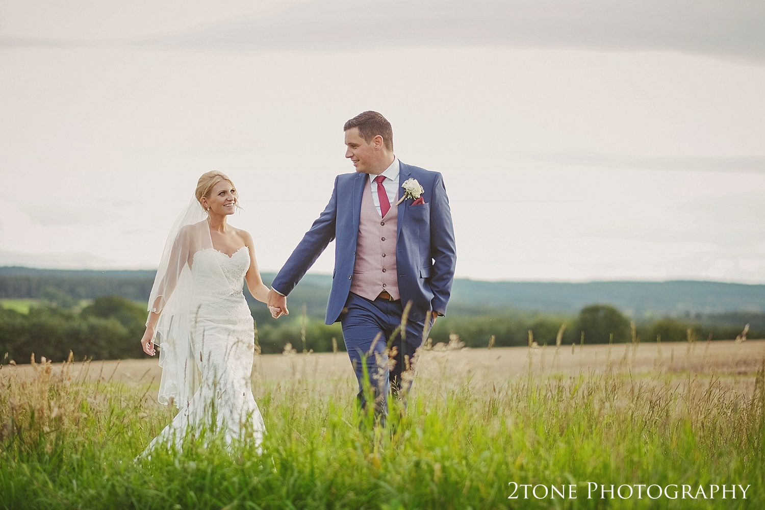 Bride and Groom inBride and groom in a country field at Healey Barn by wedding photography team, 2tone Photography www.2tonephotography.co.uk