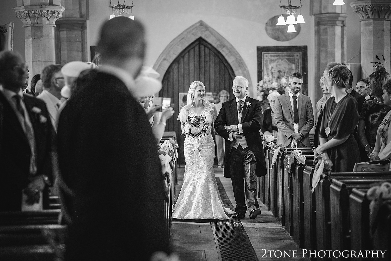 Bride walking down the aisle in Stamfordham Church.  Wedding photography at Matfen Hall by wedding photographer www.2tonephotography.co.uk