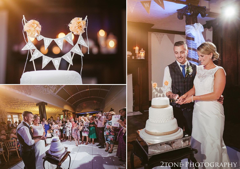 Cutting the wedding cake.  Wedding photography at Guyzance Hall by wedding photographers www.2tonephotography.co.uk