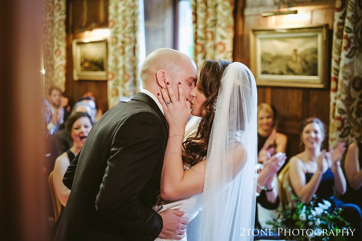 The first kiss at Ellingham Hall. Winter wedding photography by www.2tonephotography.co.uk