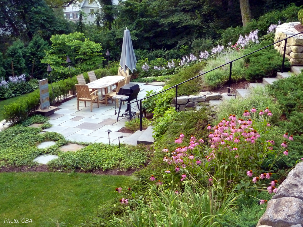 """As detailed in the 2010 article """"Hillside Havens"""" in Backyard Solutions Magazine, CBA turned what had been a neglected, overgrown hillside into unique, usable spaces. Graceful, curving stone walls tie three terraced spaces together, creating a unified design. The patio on the central terrace is the perfect spot for outdoor dining. Stairs and stepping stones connect the areas and provide an informal border for the plantings. At the bottom of the slope, an open, level lawn completes the design."""