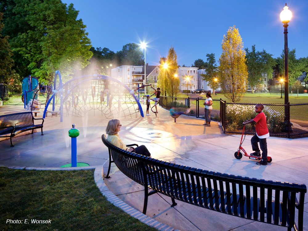 """By creating better connections and pedestrian circulation, and adding new lighting, furnishings, two lit basketball courts, and a vibrant new playground and splash pad, CBA's design revitalized this large park, exceeding the community's expectations. Areas for multiple uses were highly important in the design. Praised as """"an oasis in the city"""" and """"like night and day"""" when compared to the prior space, the park showcases CBA's ability to respond to the needs and desires of residents and create a neighborhood asset."""