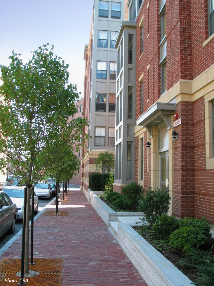 This 184-unit housing development was built on approximately two acres of vacant land. A goal for the project was to provide the City with significant open space. To achieve this, a 277 space, below grade parking garage was created with a park on its surface. Thus, the park at grade level is in reality a rooftop garden. This green space is a contemporary interpretation of the traditional South End Square.
