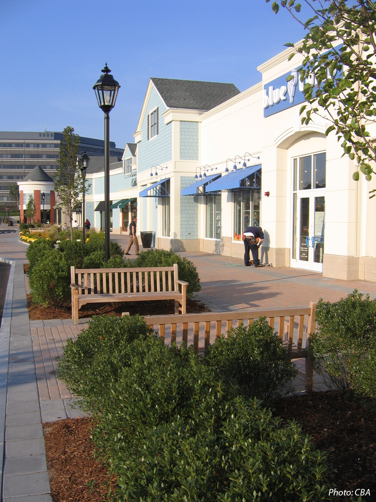 """Wayside Commons is a new """"Lifestyle Center"""" shopping mall. The design goal was to develop a beautiful and functional shopping center that embodies a spirit of place.  A generous amount of open space was landscaped to create an attractive setting for the shops. CBA designed tree-lined walks, a gazebo, vine-covered arbor, and numerous green spaces. Outdoor cafes and sitting areas throughout the development are typical site amenities."""
