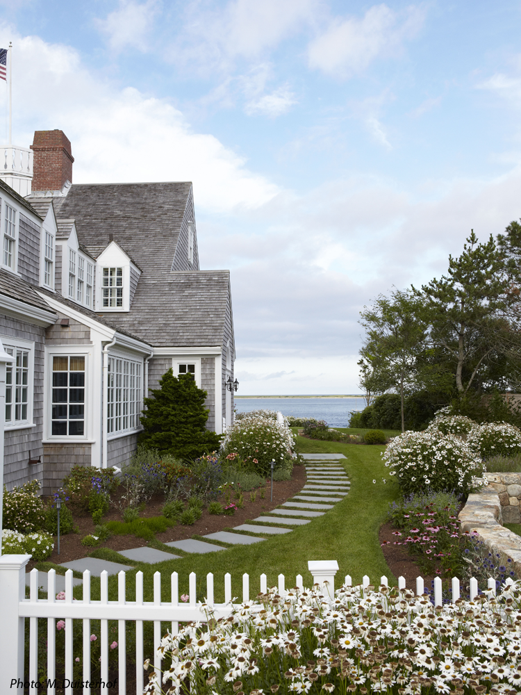 CBA created a beautiful landscape setting for this iconic home on Shore Road in Chatham which was featured in Country Living Magazine. The driveway was reconfigured to make a more inviting entrance that focuses on the house and the sea beyond. A field stone wall was designed to give the house and the immediate grounds a base on which to rest. A picket fence lined with roses defines the foreground of the house. Bluestone stepping stones welcome the guests through the arbor to the main door at the side of the house. Colorful, easy care perennials surround the house and an elevated patio at the rear of the house offers spectacular views.