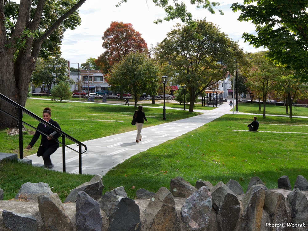 """CBA's design for this neighborhood """"commons"""" strikes a balance between refurbishing an historic greenspace and providing new activities. The site's defining diagonal walkways are joined by a meandering path connecting several new play features, selected to add a sculptural element to the site rather than the first impression being one of a playground. The many significant trees and historic stone wall around the park were protected. Paired fieldstone walls terrace the slope on both sides of the upper half of the main path, adding a dynamic element and providing more seating. Near the main entrance, a stepped wood and metal trellis shades groups of benches. The flattest area remains as open lawn for informal games."""