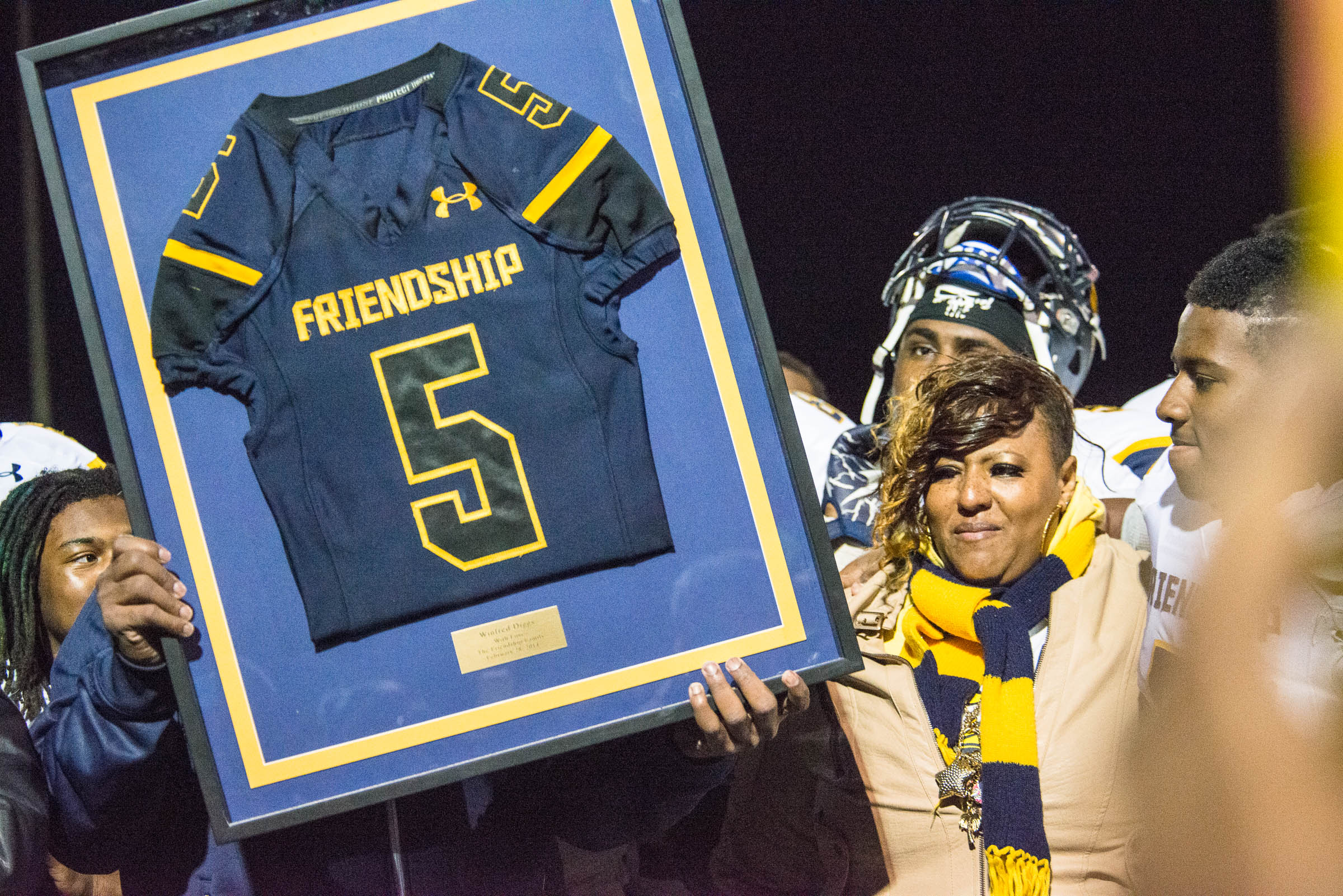 Friendship's football team honors fallen alumni players Winfred Diggs (number 5) and Marquese Meadow (number 57).