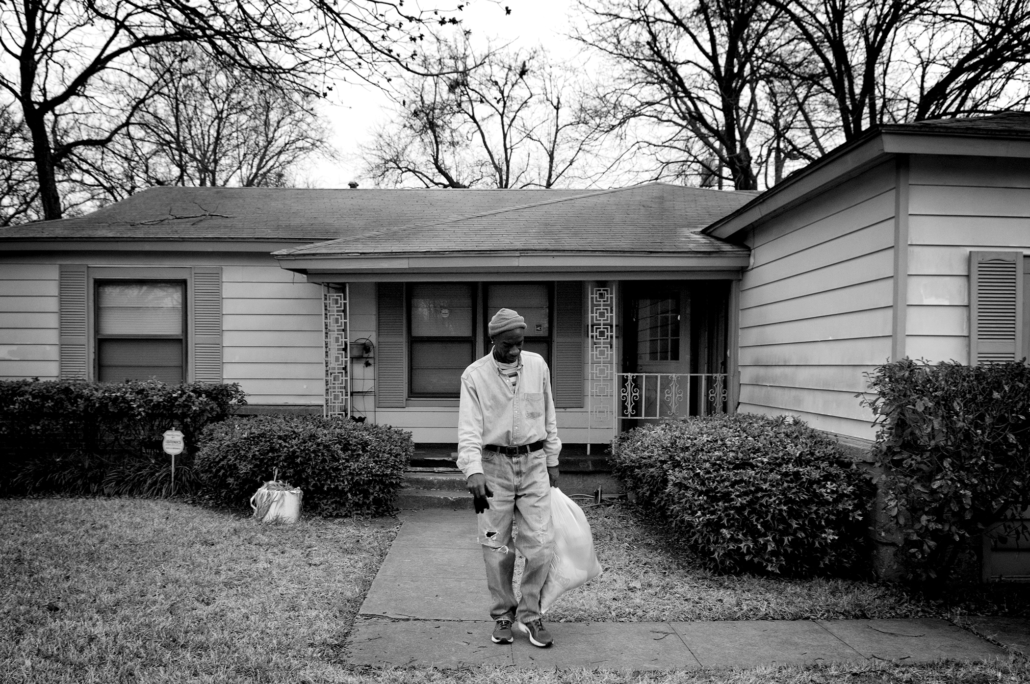 Photo by Christena Dowsett Crawford leaves his uncle's house in Oak Cliff, Texas. Crawford makes the trip to his uncle's once a week to wash clothes, and exchange for new ones.