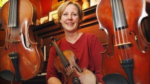 JASON HUNTER-WATERTOWN DAILY TIMES  Violin/fiddle instructor and performer Gretchen Koehler, the latest inductee into the New York State Fiddlers' Hall of Fame, sits on a piano bench with her beloved stringed instruments in her home in Potsdam.