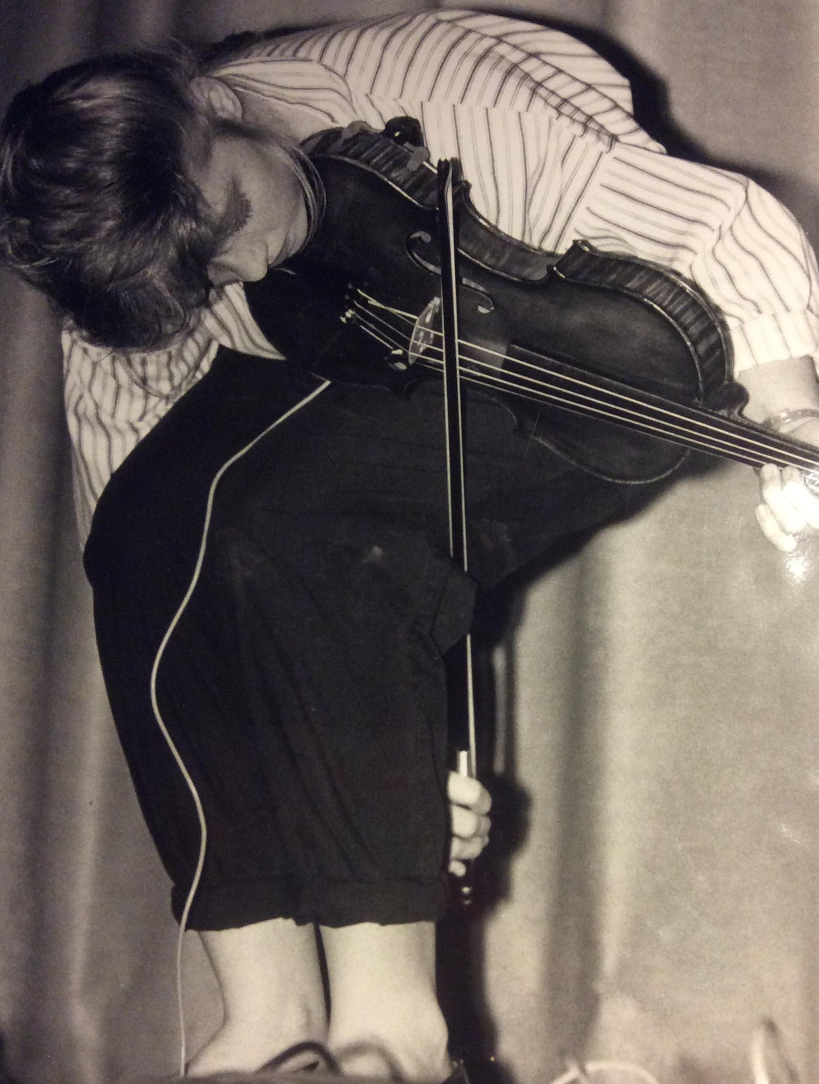 BEHIND LEGS - Keep your fiddle in regular playing position (under your chin) as you bend at the waist and head upside down.Many players elaborate on this position by separating their legs and threading the bow behind their right leg to reach the fiddle in front. Some take it a step further and balance on their left leg while lifting their right leg off the ground and bowing from underneath that leg. Whatever variation you do, be very mindful of your fragile bow while playing behind your legs.PHOTO: Rebecca Koehler, 1989