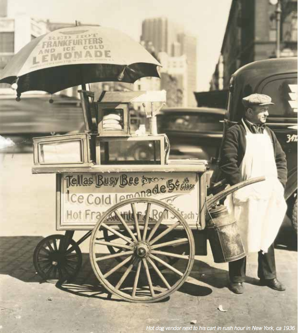 Hot dog vendor next to his cart in rush hour New York, ca 1936