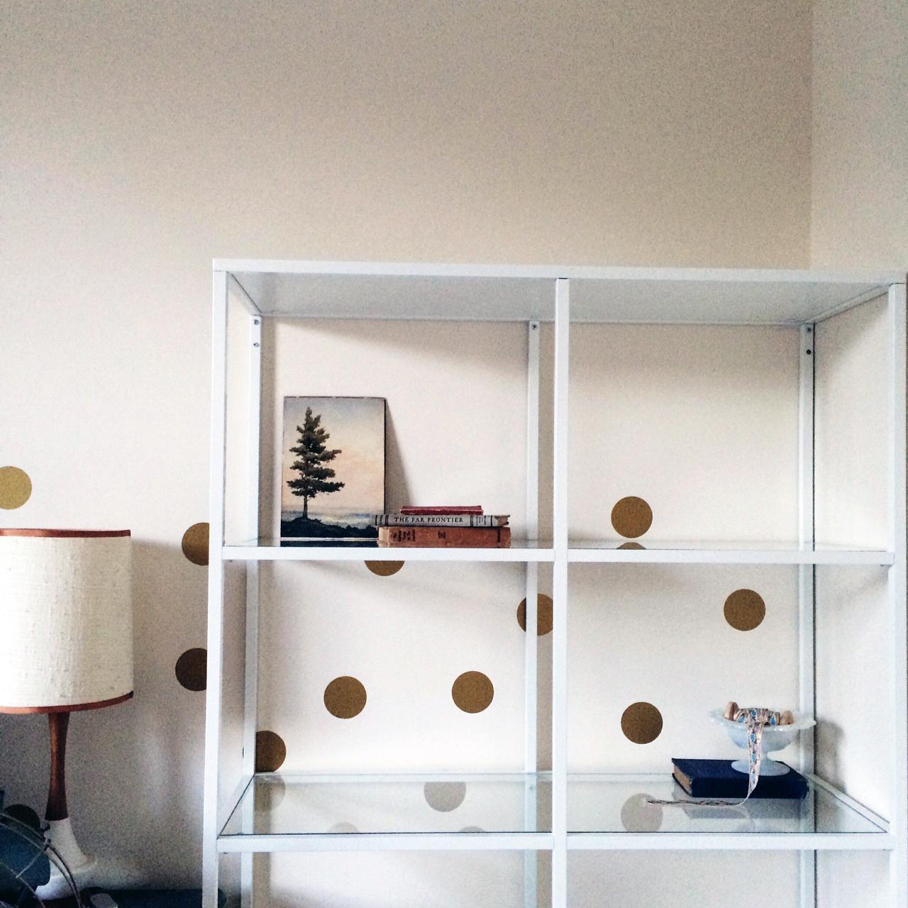 putting together IKEA bookshelves with vintage artwork