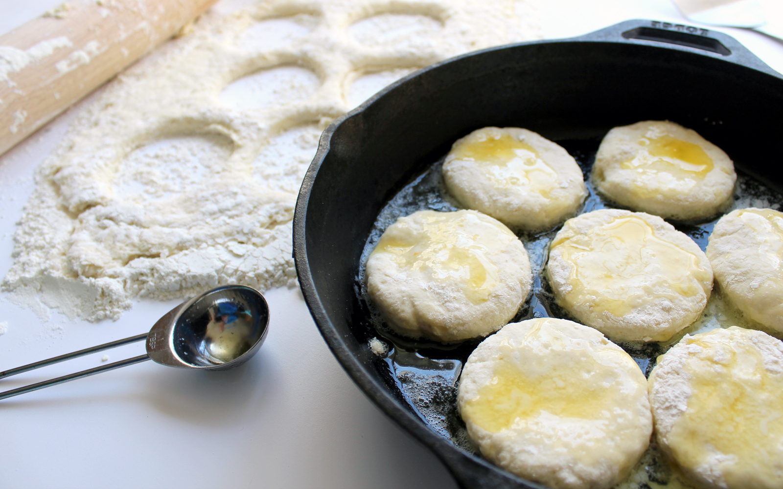 Biscuits ready to go in the oven with butter poured over the top