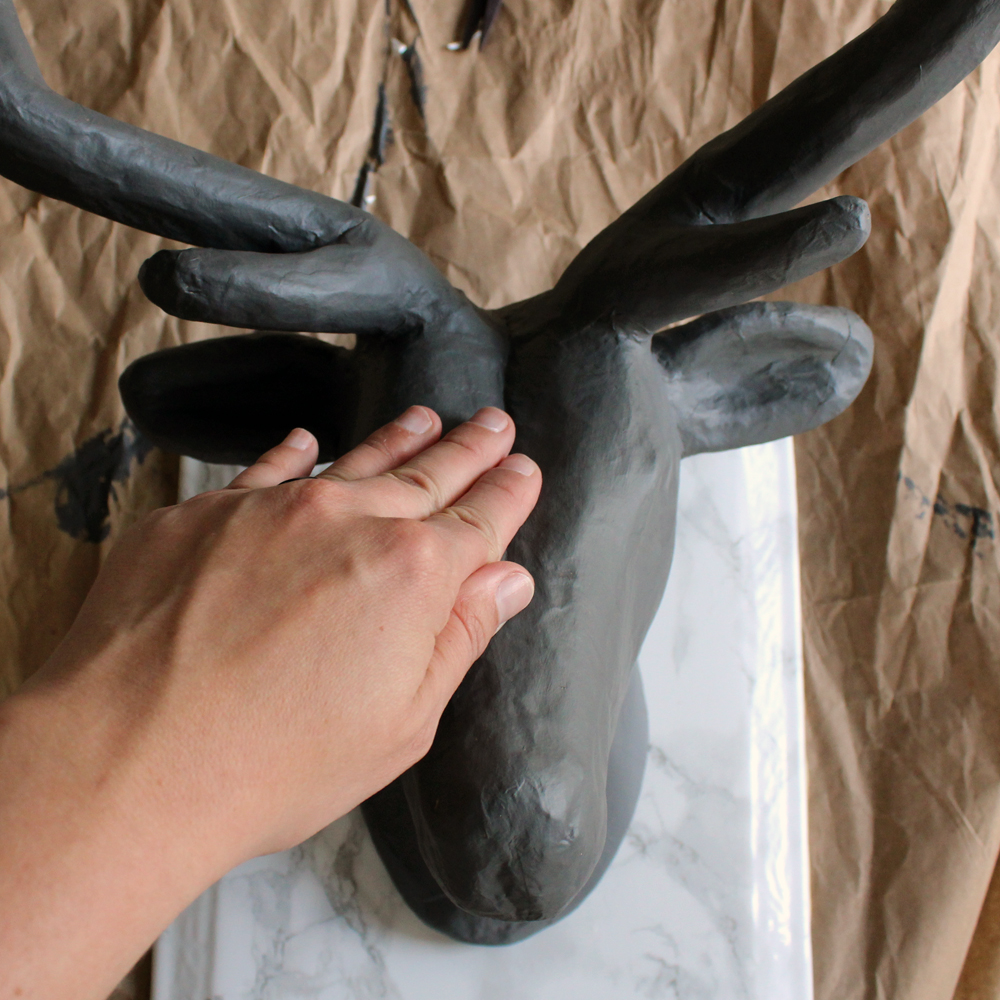 use hot glue gun to attach deer head to plaque