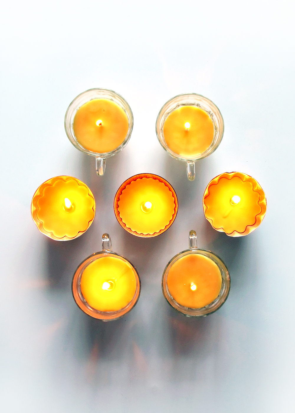 homemade beeswax candles in vintage teacups and jello tins