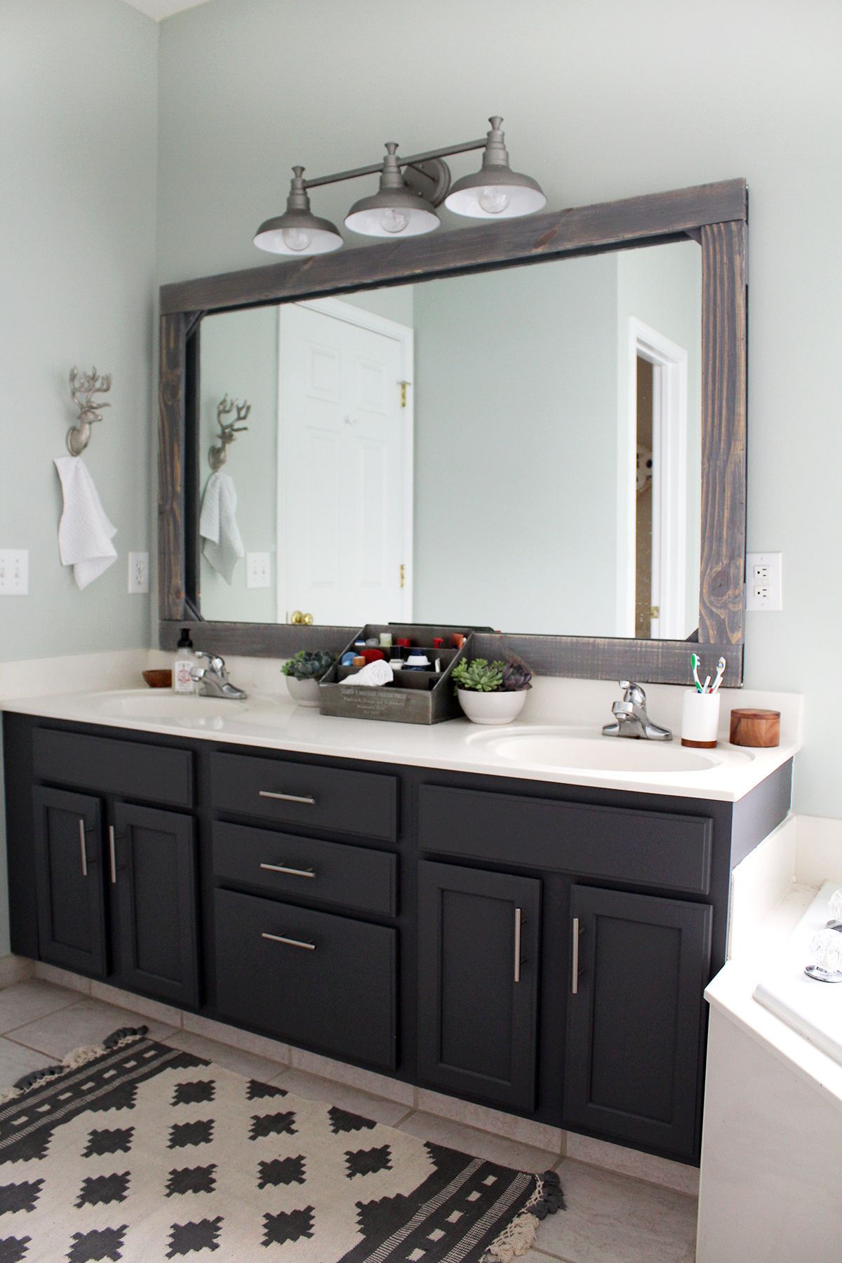 bathroom refresh for $300--painted dark grey cabinets, mirror frame, and a new light fixture #homedesign #DIYdecor #bathroom