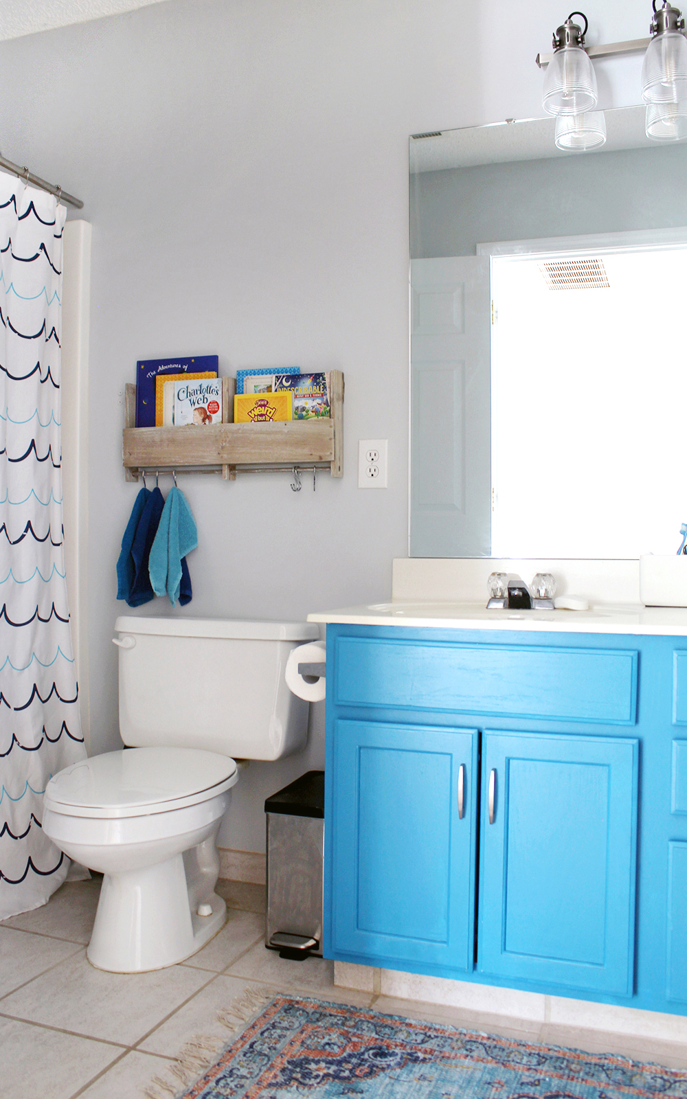 cheerful kid's bathroom with SW Misty walls and bright blue cabinet
