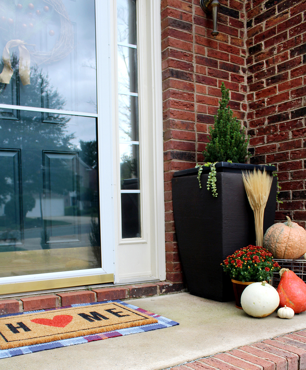 Love the layered rug. Decorate a Fall front porch with mums, pumpkins, and wheat--check out these practical tips! #autumndecor #falldecor #pumpkins