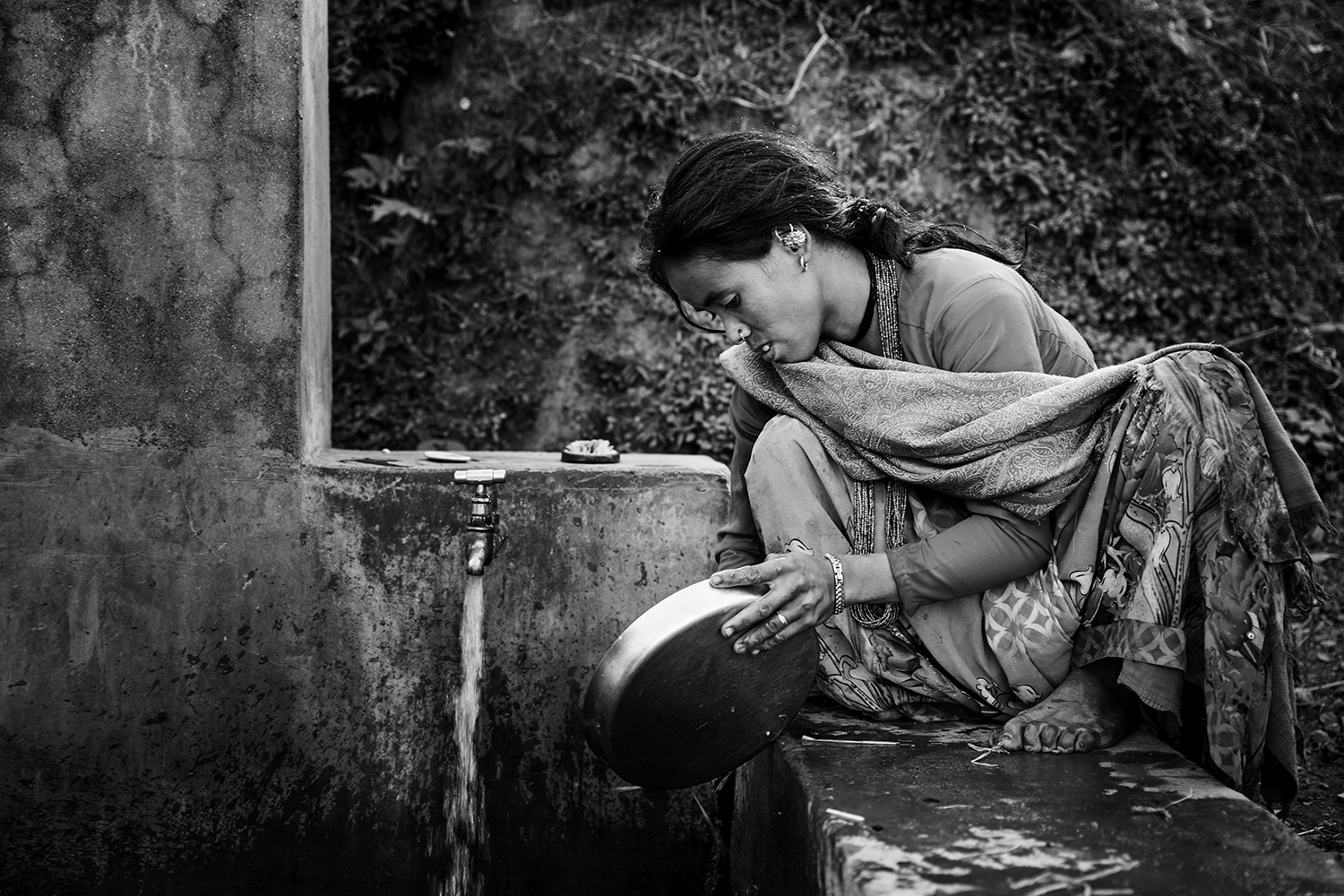 A young woman washes the dishes after lunch on a water supply tap. These taps are part of RVWRMP's support program.
