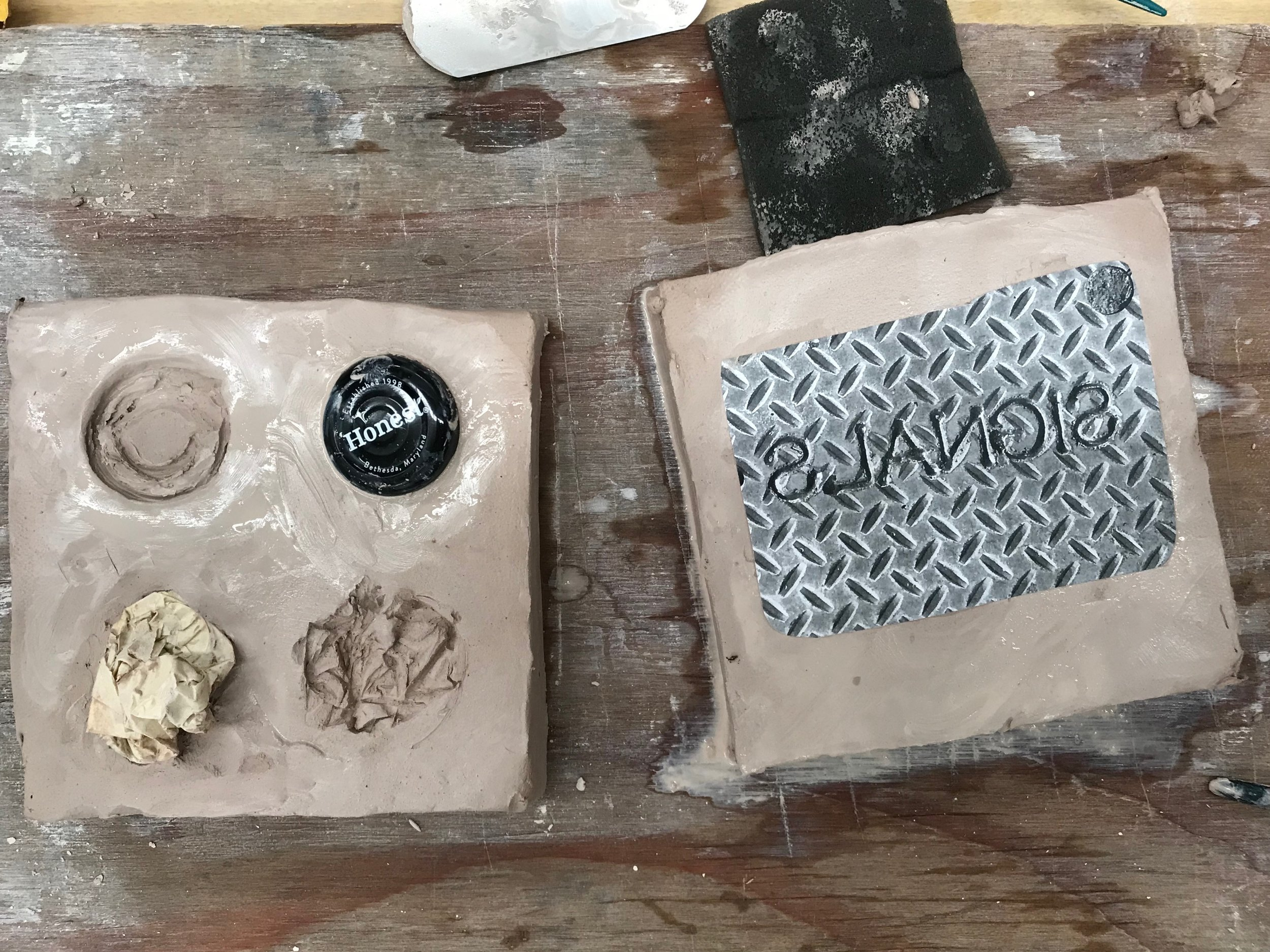Mold-making tiles with items pressed into clay, as with a stamp.