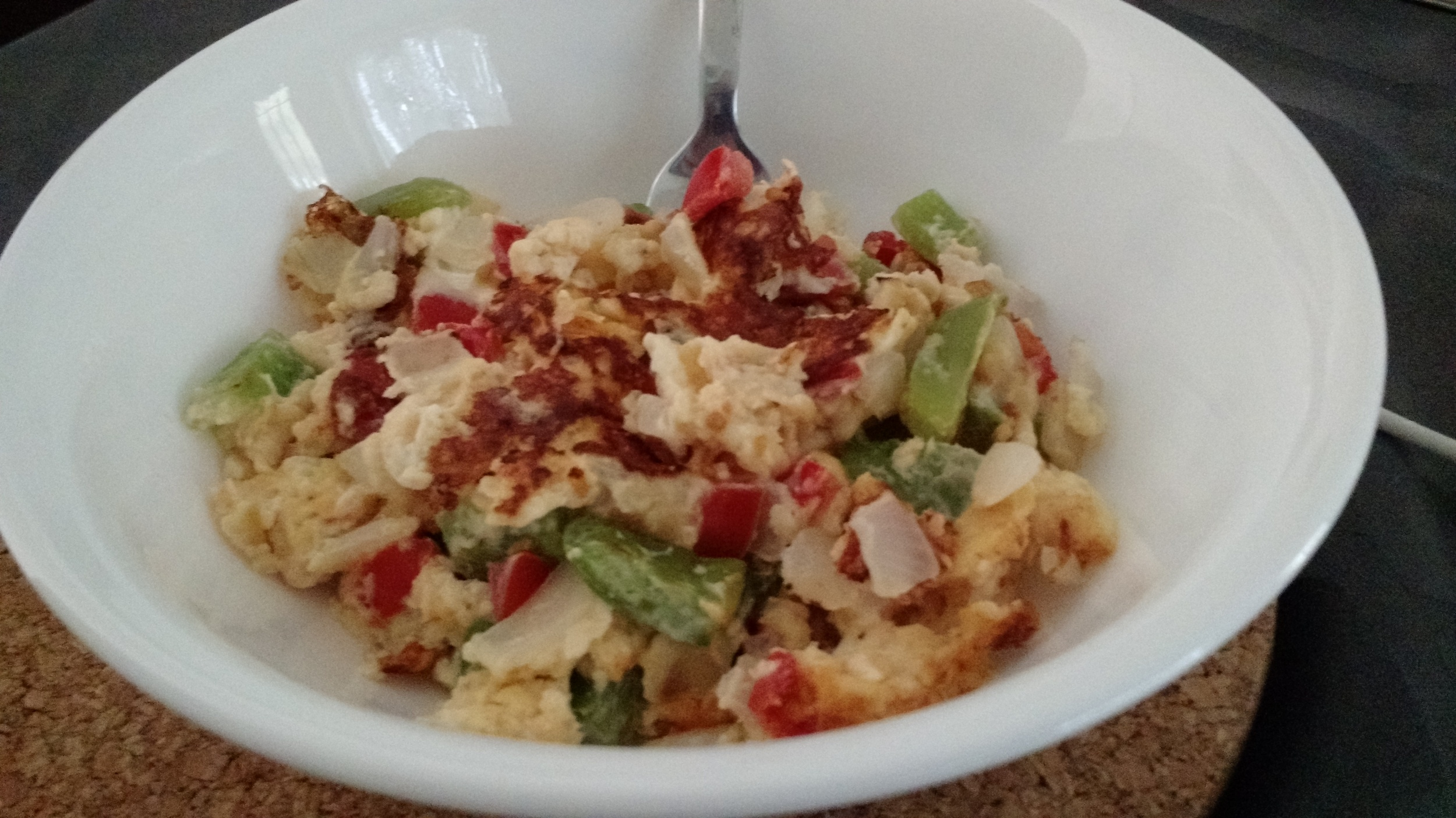 This is breakfast: one egg, bell peppers, onions, tomatoes, and cheese scrambled together.
