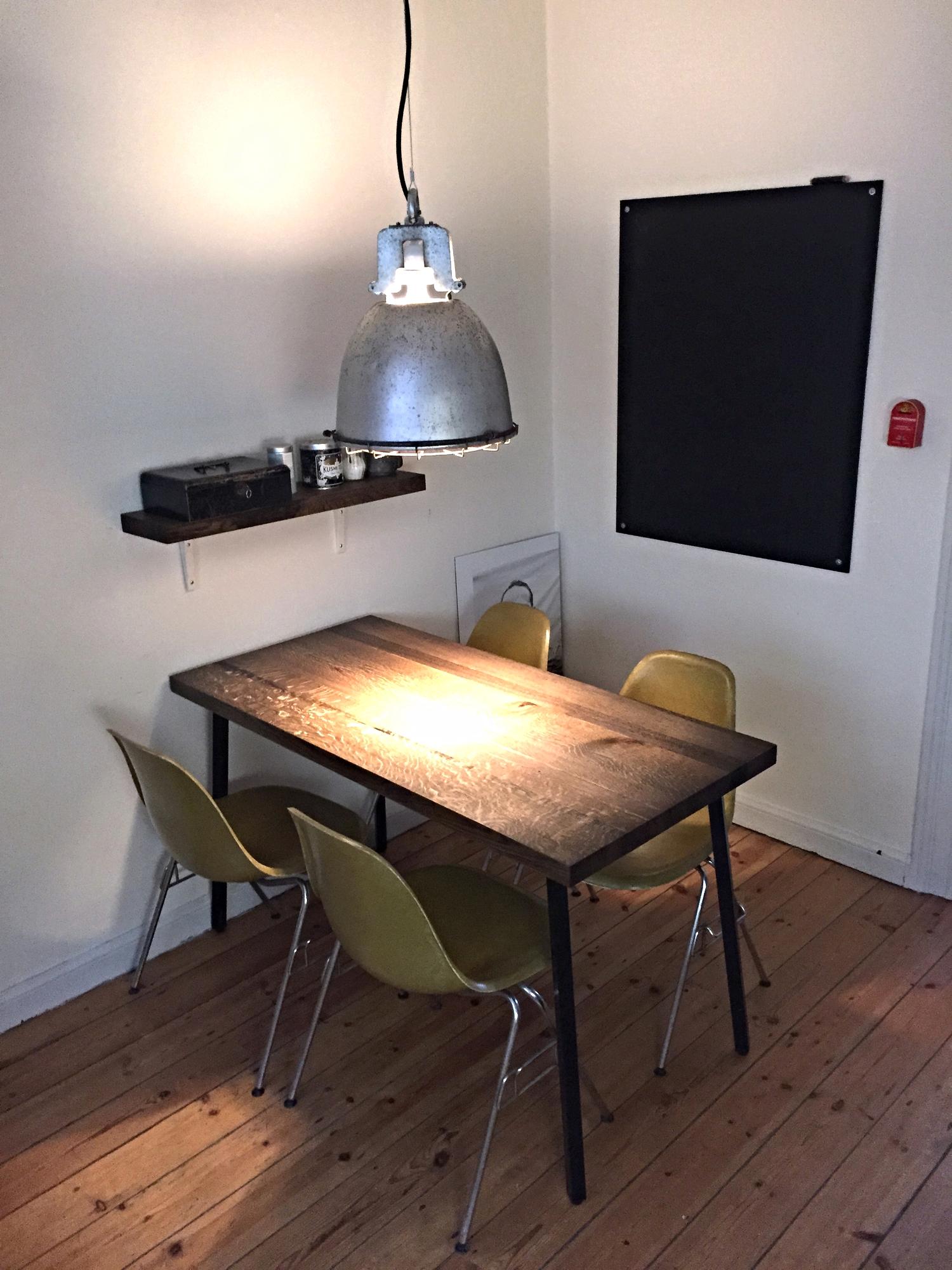 """Bordet er nu færdigbehandlet og står på sin plads. I tilkøb til bordet, lavede jeg en lille hylde i egetræ, som fik samme behandling som bordet. Som en del af denne """"opgradering"""" af spisepladsen i mit køkken, opgraderede jeg også en gammel lampe, som har hængt i et smedeværksted et sted i jylland. Det havde sine udfordringer, at få det til at fungerer, men det lykkedes, og jeg er alt i alt godt tilfreds med resultatet."""