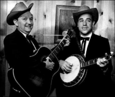 """Lester Flatt by Mary Kennedy Brown       My great-grandparents, Pappy and Mammy, moved from the mountains of East Tennessee, where houses were mostly black tar paper, down South to Pulaski, a foreign land with televisions and such. They lived in a bedroom in my grandparent  's house that had been the den, so they had a t.v. at the ready. Mammy  's maiden name was Flatt, and she was kin to Lester Flatt somehow. She resented that he was in that box on Saturdays and would not speak to her. She would holler,""""I see you, Lester. I know you see me, and you better speak to me!"""" This would go on for the entire half-hour program. I guess she died thinking Lester was the biggest snob in the Flatt family. She may have been right."""