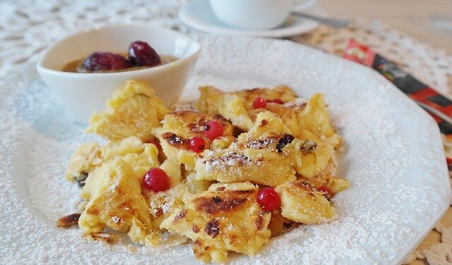 Kaiserschmarrn - 1 Tbsp Butter5 Eggs6 oz. (180g) Flour1.5 cup (350ml) Milk3 oz. (90g) Raisins1 pinch Salt1 grated Lemon rind1 Tbsp Sugar to caramelize- Separate yolk from egg white.- Beat the yolk, milk, salt, sugar and lemon rind in a bowl until well combined.- Slowly add flour while continuing to beat until you have a soft dough, add raisins or a shot of rum.- Beat the egg white until stiff and fold it into the dough.- Heat the butter in a pan, add the dough and fry on medium heat until the bottom is golden.- Tear the cooked dough into bite-sized pieces and flip them over.- Continue to fry and turn until all the pieces are golden brown on both sides.- Scatter the sugar over the Schmarrn and mix it through a few times so that the sugar caramelizes. Sprinkle lightly with icing sugar and serve in the pan accompanied by vanilla ice-cream.