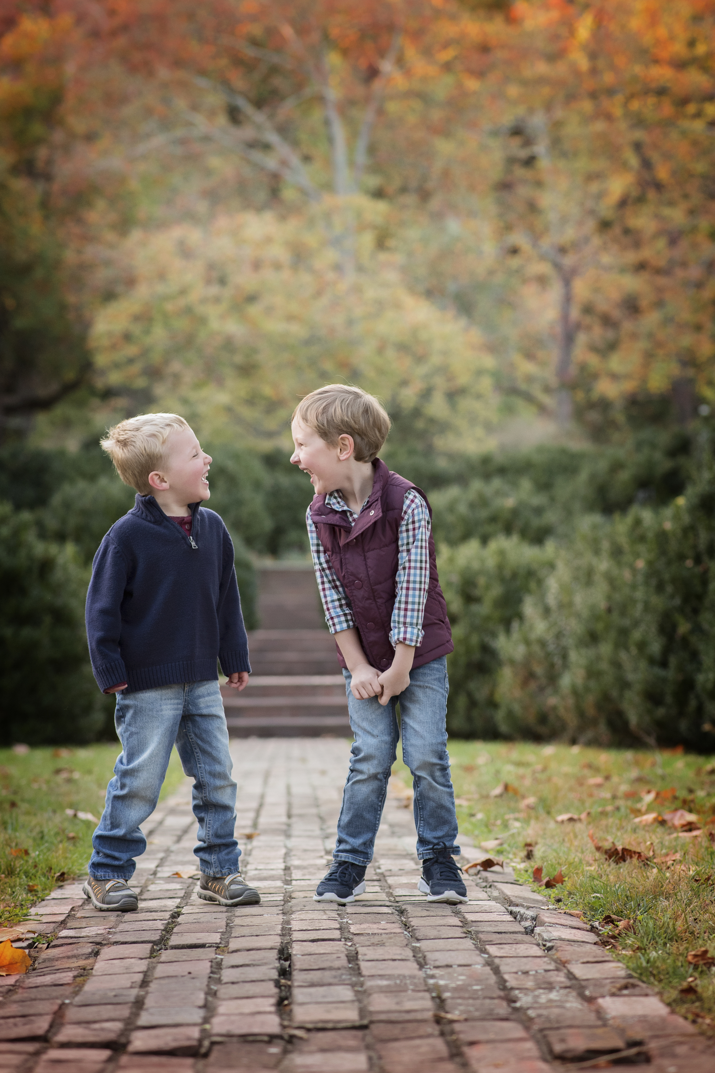 childhood best friends laughing together on brick sidewalk kate montaner photography chlidrens lifestyle photographer