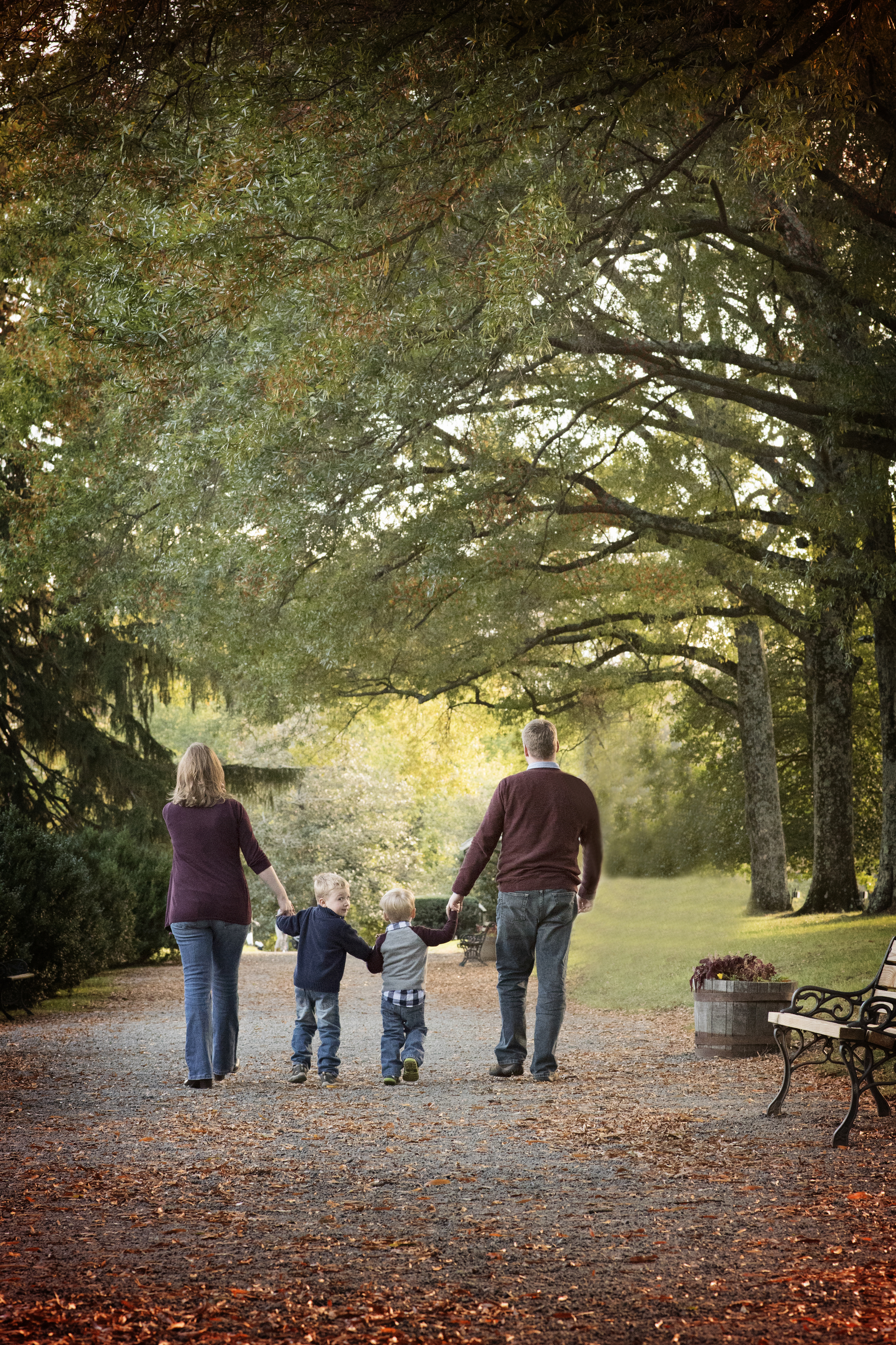 Family walking in park with fall trees and leaves Springfield VA Family Photographer Kate Montaner Photography