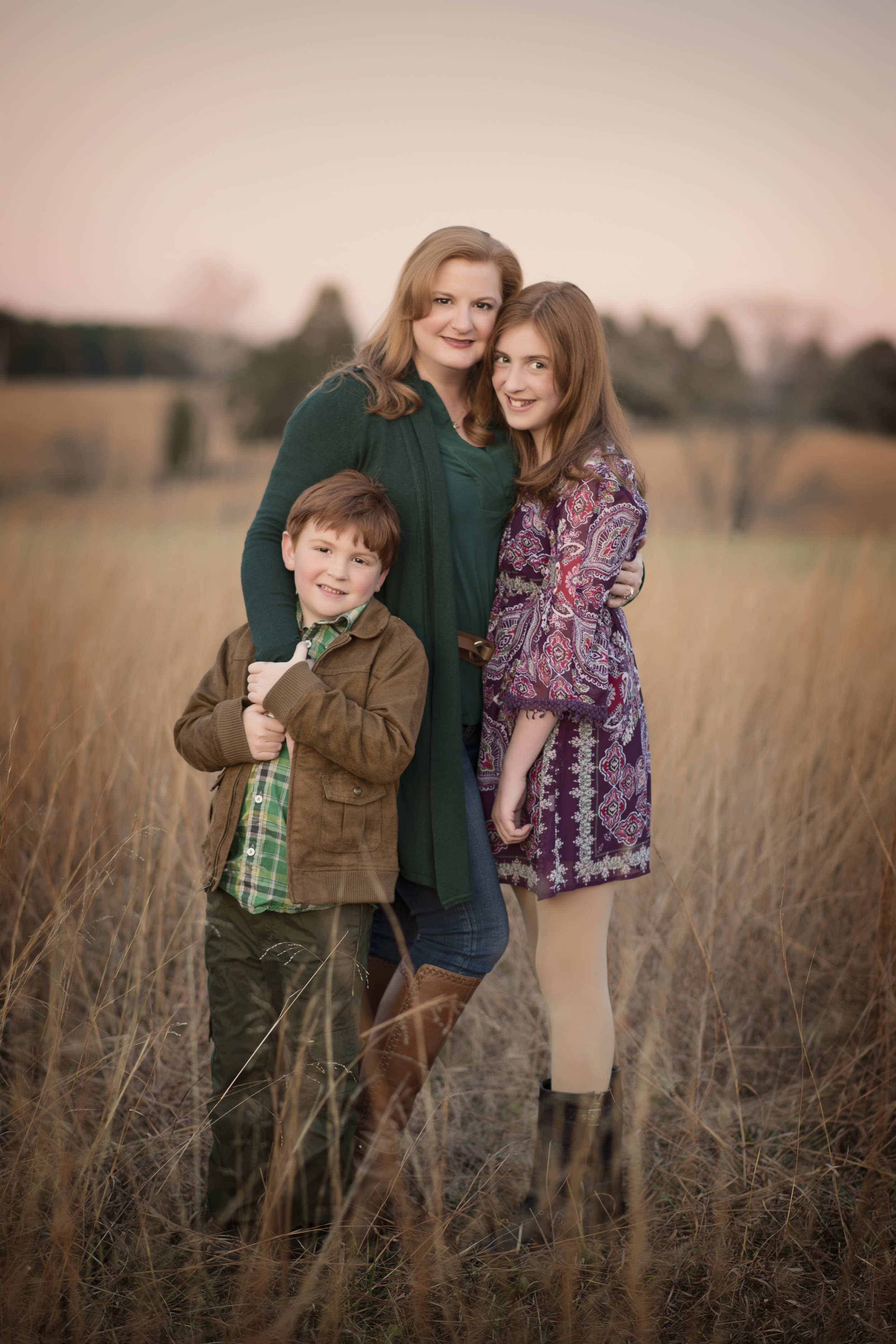 Mother with son and daughter embrace at sunset Kate Montaner Photography
