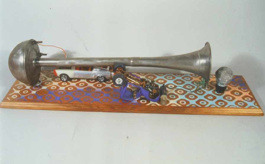 "Car-Chestra, 24""x6""x6"", truck horn, model cars, microphone head, acrylic & wood, 2007"